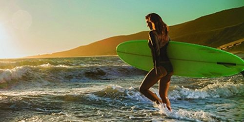 Woman With Surfboard at Beach   Teplis Travel