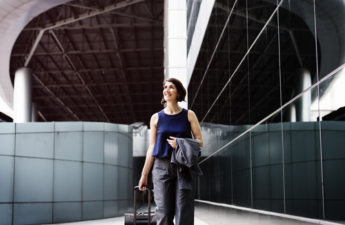 Relaxed Female Business Traveler with Rolling Suitcase   Teplis Travel