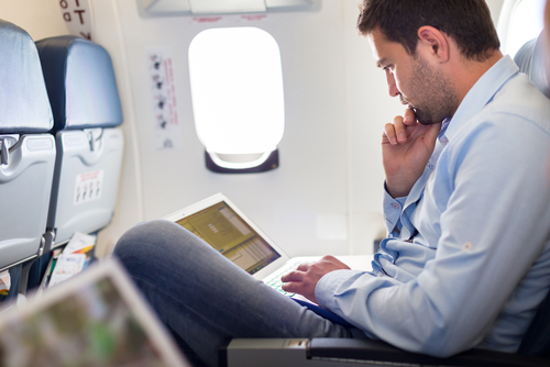 Corporate Traveler Using Laptop on a Plane | Teplis Travel